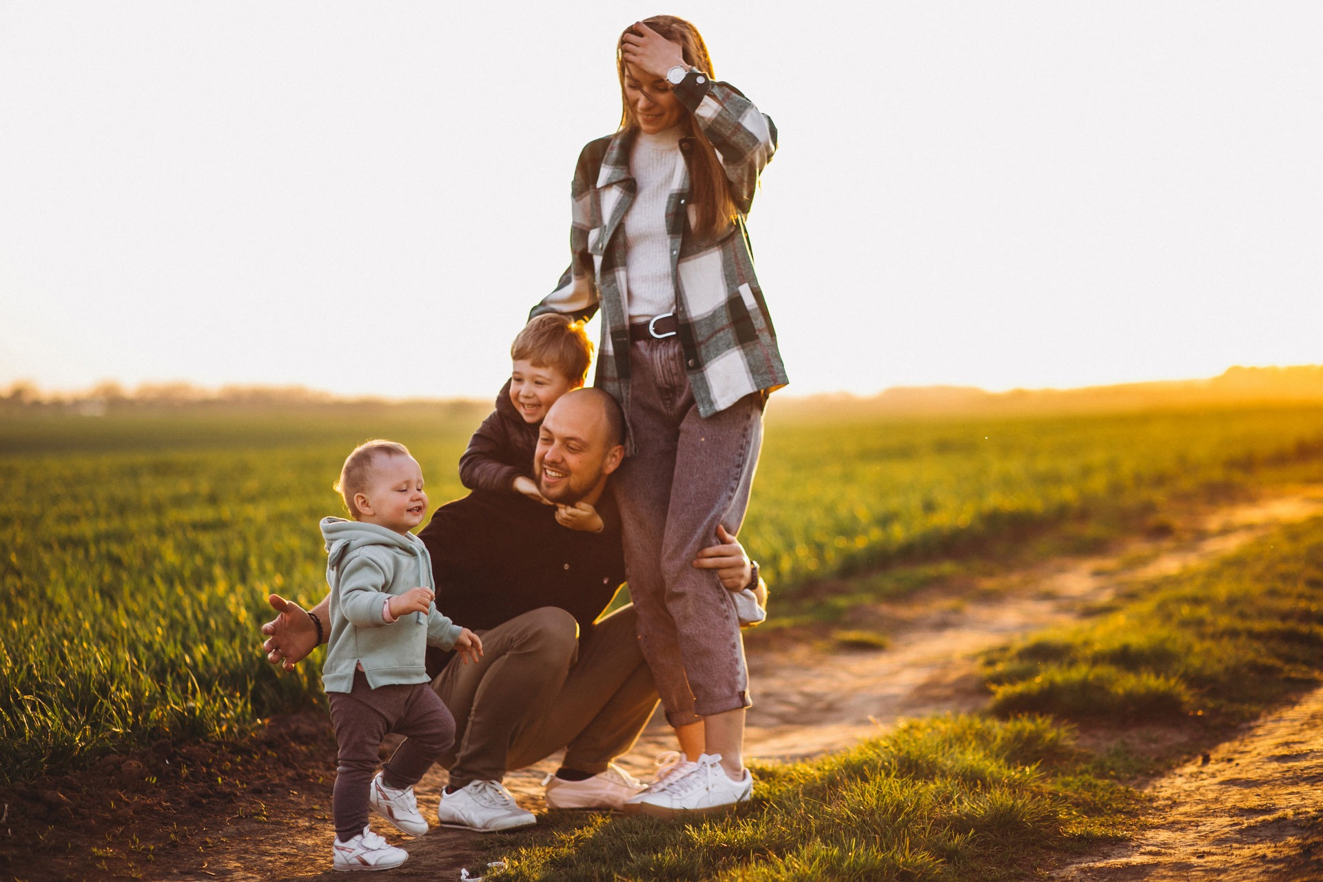 Happy family having fun in the field on the sunset